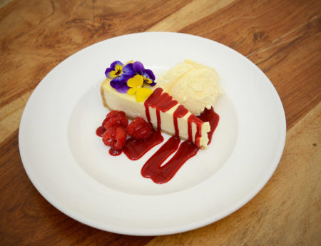 Cheesecake with a mixed berry coulis and edible viola flowers